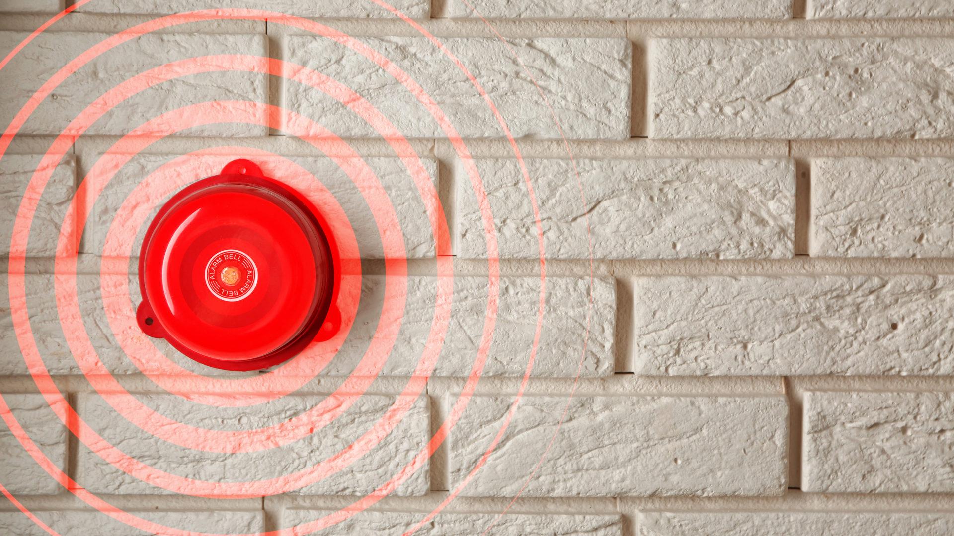 Ringing alarm bell on brick wall indoors